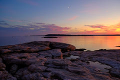 Moonrise and colorful sunset on the rugged and rocky coast Royalty Free Stock Image