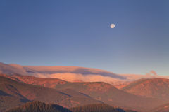 Moonrise in the mountains at dawn Stock Photo