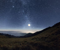 Moonrise in the mountains. Starry night sky with rising full moon over the misty mountains Royalty Free Stock Images