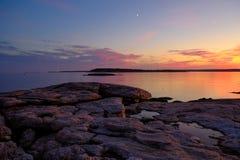 Moonrise och färgrik solnedgång på kraftfullen och den steniga kusten Royaltyfri Bild