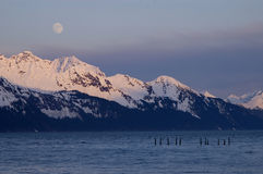 Moonrise over Alaskan Mountain Range. A moonrise over the Alaskan Mountain Range with the Resurrection Bay and some pier pilings in the foreground Stock Photo