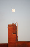 Moonrise Over Building. Moonrise over brick building in Montreal, Quebec royalty free stock photography