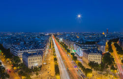 Moonrise over the Champs-Elysees in Paris at nightfall. The moon rises above the Champs-Elysees in Paris at nightfall stock photo