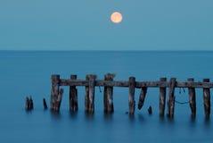 Moonrise over een meer bij zonsondergang Stock Foto's