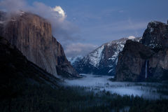 Moonrise over El Capitan. A fullmoon moonrise over El Capitan during sunset.  Bridalviel Falls, milky cloud cover in the valley Stock Photos