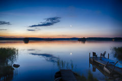 Moonrise over lake. Jetty with chairs and rowboat at shore stock photos