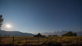 Moonrise over Mormon Row in Wyoming. The stars and moon light up Mormon Row and the Grand Teton Mountain range at night Royalty Free Stock Photos