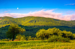 Moonrise over the mountain in rural area at sunset. Moonrise over the mountain ridge.  rural valley in sunset light. beautiful countryside landscape. blu sky Stock Photo