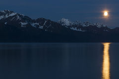Moonrise over mountains with full moon reflection. Moonrise over snow-covered mountains with full moon reflection on water stock photo