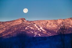 Moonrise over Mt. Mansfield, Stowe, Vermont, USA. A large moon rising over Mt. Mansfield at sunrise in Stowe, Vermont, USA Royalty Free Stock Image