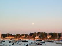 Moonrise over New England Harbor with Sailboats Royalty Free Stock Photography
