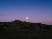 Moonrise over rocks. A full moon rises into a sunset at Rocky Peak park Stock Photos