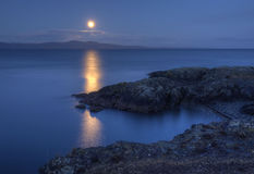 Moonrise Over San Juan Island USA from Canada. A full moon rises above a layer of cloud over San Juan Island, USA with a rocky shore and beach with logs in the royalty free stock photo