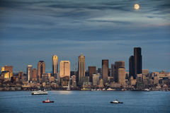 Moonrise Over Seattle, Washington. A full moon comes up over Elliott Bay and the Seattle Skyline. Tub boats and ferries work the waterfront area during this Royalty Free Stock Images