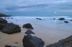 Moonrise på en stenig kust med fyren Arkivbild