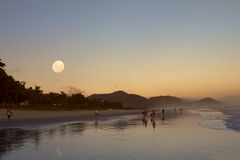 Moonrise and sunset at the beach Royalty Free Stock Photography