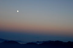 A moonrise at sunset over the mountains Royalty Free Stock Image
