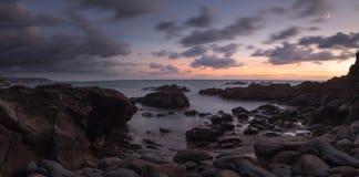 Moonset和日落在新月形海湾在拉古纳海滩靠岸 免版税库存图片