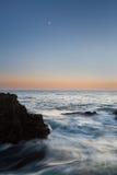 Moonset över stenigt hav Arkivbild