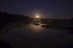 Moonset över träsket Arkivfoton