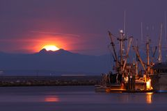 Moonset at Dawn, Steveston. A long exposure of Steveston Harbor In the early morning with commercial fishboats tied to the docks as the full moon sets behind the Royalty Free Stock Photos