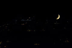 Moonset. A gibbous moon close to set down over a urbanized hill Stock Images