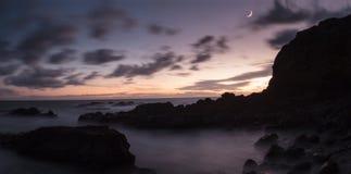 Moonset och solnedgången på Crescent Bay sätter på land i Laguna Beach Arkivfoto