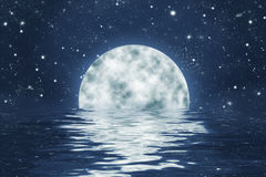 Moonset over ocean with full moon on blue night sky. Moonset over water with waves, with full moon on blue night sky with stars Royalty Free Stock Photography