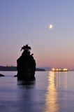 Moonset and siwash rock in Stanley Park Royalty Free Stock Photo