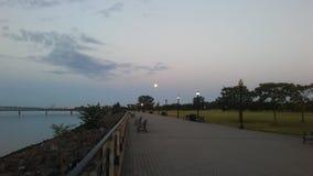 Moonset under soluppgång i purpurfärgad himmel Fotografering för Bildbyråer