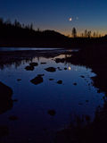 Moonset with Venus, reflected in lake. Moon and Venus, setting over silhouetted mountain pines. Reflection of both in glassy water. California Alps, Sierra Stock Photo