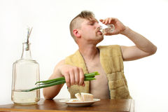 Moonshine. The man drinks moonshine and has a snack fat and an onions stock images
