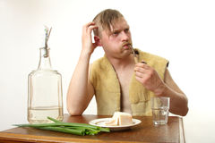 Moonshine. The man drinks moonshine and has a snack fat and an onions royalty free stock image