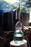 Moonshine flows from a homemade moonshine apparatus into a glass jar. Production of moonshine in Russia royalty free stock photo