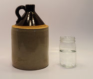 Moonshine jug and mason jar Stock Photography