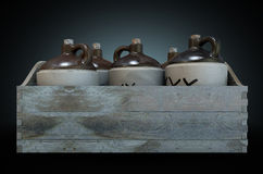 Moonshine In Wooden Crate. A 3D render of a collection of five vintage moonshine jugs in a wooden carry crate on an isolated dark studio background royalty free stock photo