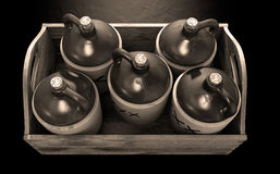Moonshine In Wooden Crate. A 3D render of a collection of five vintage moonshine jugs in a wooden carry crate on an isolated sepia studio background royalty free stock image