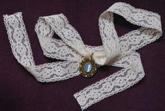 Moonstone-halsband met wit kant op purpere fluweelachtergrond Stock Afbeeldingen