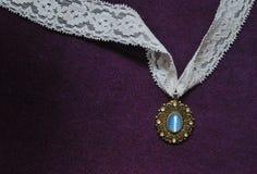 Moonstone necklace with white lace on purple velvet background Stock Image