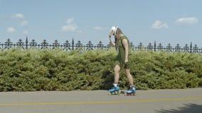 Moonwalk de fatura fêmea nas lâminas do rolo no parque vídeos de arquivo