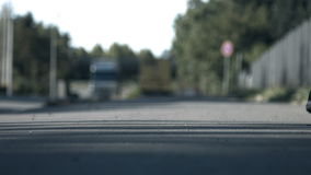 Moonwalking in Traffic. A shot of a pair of sneakers moonwalking while traffic passes by in the background. Filmed on a sunny day from a ground perspective stock footage