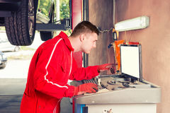 Moor mechanic checking the readout on a computer. Hooked to a car elevated on a hoist as he performs a service and tune up in a garage workshop Stock Photos