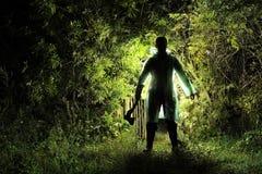 Moordenaar met een bijl in de tuin stock afbeelding