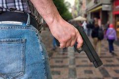 Moordenaar met pistool en menigte van mensen op de straat stock afbeelding