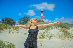 Moore Lighthouse woman. Carefree woman with open arms on white beach with dunes of Geraldton, Western Australia. The historic Moore Lighthouse Point built in Royalty Free Stock Image