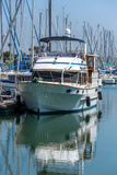 Moored boat and its reflection. In marina Stock Photos