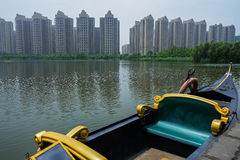 Moored boat in lake of modern city Royalty Free Stock Photos
