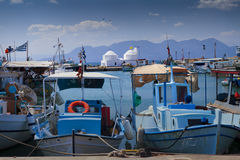 Moored boats in Aegina harbour, Greece. Moored boats and little white church in Aegina harbour, Greece royalty free stock photos