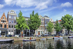 Moored boats and ancient gabled houses in Amsterdam Stock Photo