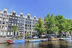 Moored boats and ancient gabled houses in Amsterdam Stock Images